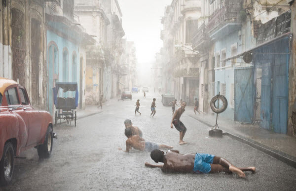 عکسی که شادی و نشاط کودکان را در هاوانا در یک تابستان گرم بعد از بارش باران نشان میدهد