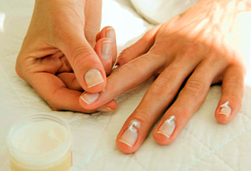 getty_rf_photo_of_woman_putting_lotion_on_nails