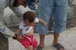 بازی نوزاد یک داعشی با سر بریده + عکس